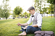 Confident mature businessman with laptop in the city park sitting on grass - HAPF01734