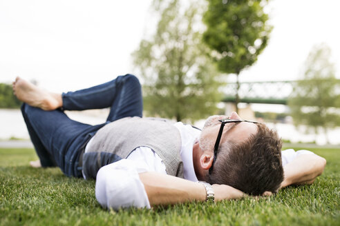 Mature businessman in the city park lying on grass - HAPF01740