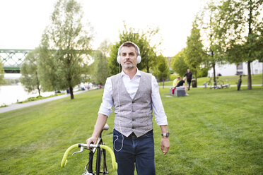 Confident mature businessman with bicycle and headphones in the city park - HAPF01743