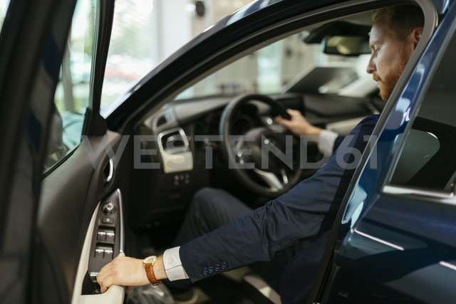 Businessman testing car in car dealership - ZEDF00656