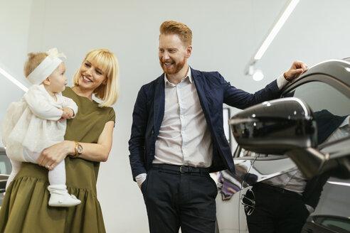 Family in car dealership choosing family vehicle - ZEDF00665