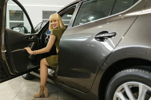 Blond woman choosing new car in car dealership - ZEDF00671