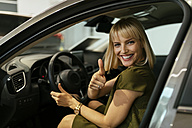 Blond woman choosing new car in car dealership - ZEDF00674