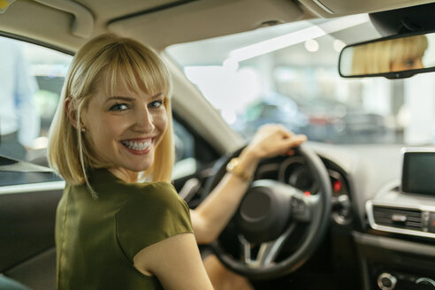 Blond woman choosing new car in car dealership - ZEDF00677