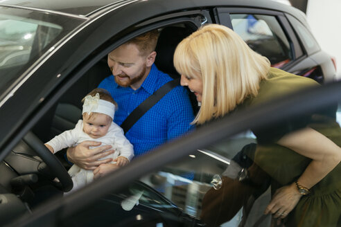 Family choosing new family vehicle in car dealership - ZEDF00680