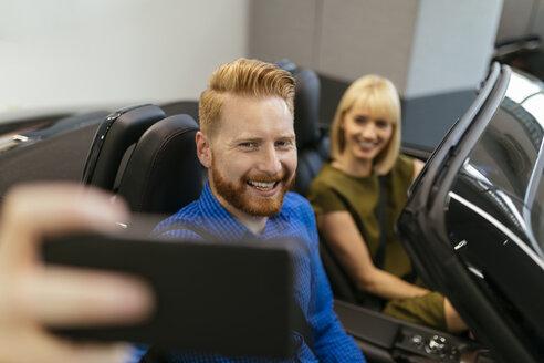 Couple taking selfies, sitting in convertible in car dealership - ZEDF00689