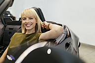 Blond woman sitting in convertible at car dealership - ZEDF00692