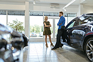 Couple looking for a new car in car dealership - ZEDF00698