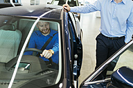 Salesman advising customer in car dealership - ZEDF00701