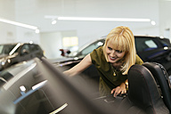 Blond woman looking at convertible in car dealership - ZEDF00713