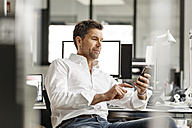 Businessman at desk in office using cell phone - PESF00695
