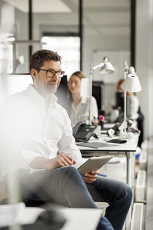 Businessman at desk in office using tablet - PESF00701