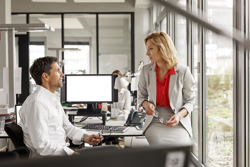 Businesswoman and businessman discussing at desk in office - PESF00710