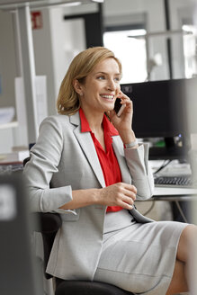 Businesswoman at desk in office on cell phone - PESF00713