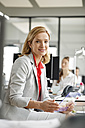 Portait of smiling businesswoman at desk in office holding futuristic tablet - PESF00716