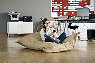Young woman with cell phone sitting in bean bag in office - PESF00722