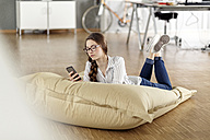 Young woman with cell phone lying in bean bag in office - PESF00725