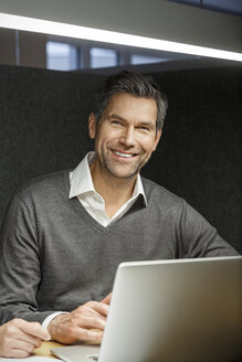 Portrait of smiling businessman with laptop in meeting box - PESF00737