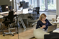 Businesswoman with beer bottle and laptop in office - PESF00743