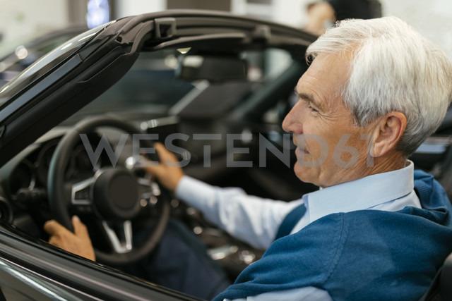 Senior man testing convertible in car dealership - ZEDF00717