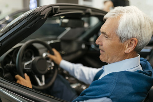 Senior man testing convertible in car dealership - ZEDF00717
