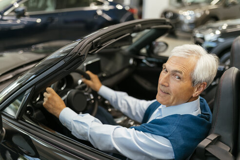 Senior man testing convertible in car dealership - ZEDF00720