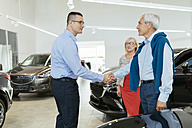 Senior couple couple talking with salesperson in car dealership - ZEDF00723