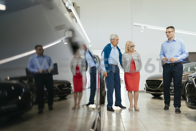 Senior couple couple talking with salesperson in car dealership - ZEDF00732