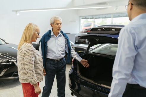 Senior couple couple talking with salesperson in car dealership - ZEDF00735