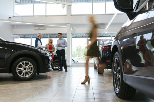 Car dealer advising customers with woman walking in foreground - ZEDF00741