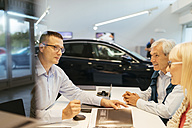 Salesperson advising couple in car dealership - ZEDF00744
