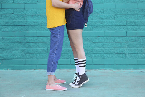 Young couple kissing in front of blue brick wall, partial view - RTBF00912