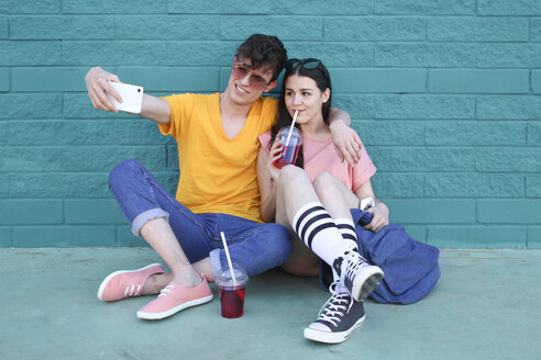 Young couple with soft drinks taking selfie with smartphone in front of blue brick wall - RTBF00915