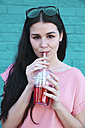 Portrait of young woman drinking soft drink - RTBF00921