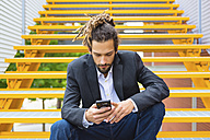 Young businessman with dreadlocks sitting on stairs using smartphone - MGIF00015