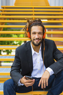 Portrait of young businessman with dreadlocks listening music with headphones and cell phone - MGIF00018