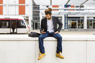 Young businessman with dreadlocks using smartphone while waiting at station - MGIF00021