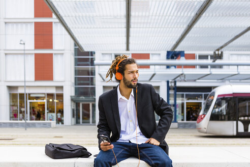 Young businessman with dreadlocks listening music with headphones and cell phone at station - MGIF00024