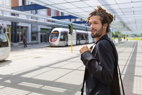 Portrait of young businessman with dreadlocks waiting at station - MGIF00027