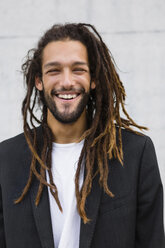 Portrait of smiling young businessman with dreadlocks - MGIF00033