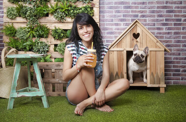 Woman and french bulldog in front of dog house and vertical garden - RTBF00926