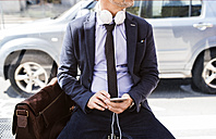 Businessman with smartphone and headphones waiting at the bus stop - HAPF01749