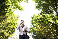Mature businessman with coffee and smartphone in city park - HAPF01755
