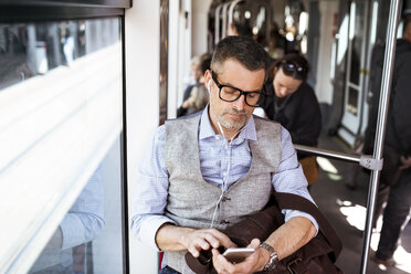 Businessman with smartphone and earphones travelling in tram - HAPF01764