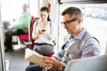 Businessman in tram reading book - HAPF01767