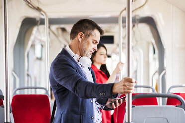 Businessman with smartphone and headphones travelling by bus - HAPF01770