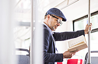 Man in bus reading book - HAPF01773