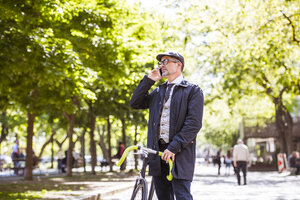 Mature businessman with bicycle and smartphone in the city - HAPF01779