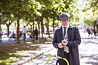 Mature businessman with bicycle and smartphone in the city - HAPF01782