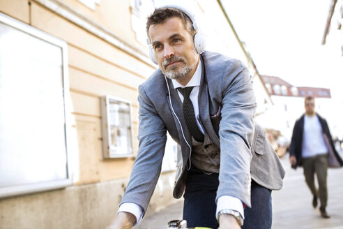 Mature businessman with headphones riding bicycle in the city - HAPF01785